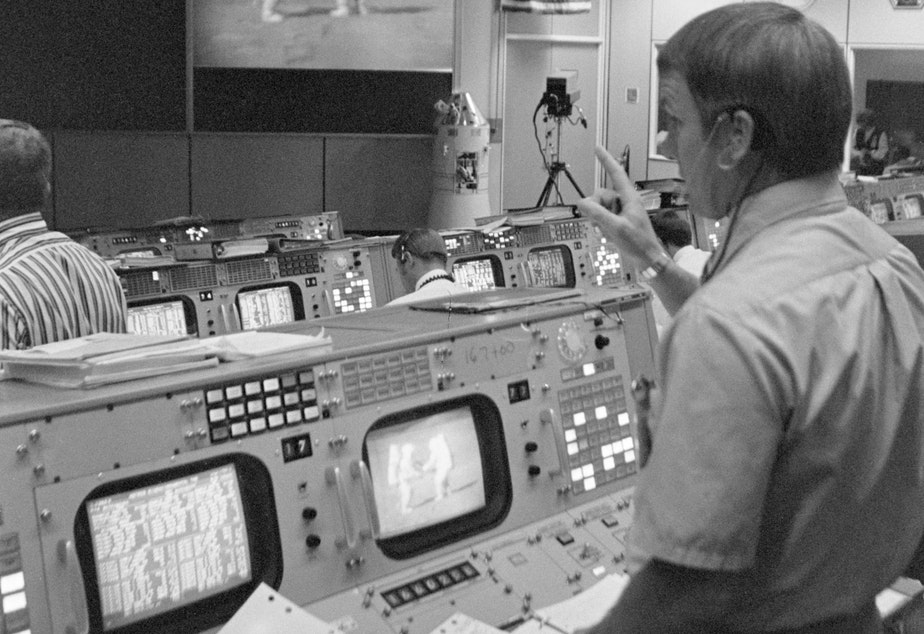 caption: A NASA flight manager watches the Apollo 15 astronauts as they work on the moon's surface.