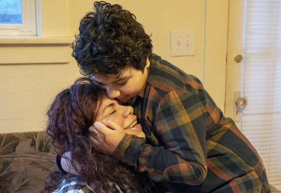 caption: Carolina Landa hugs her son, Zach, in their living room before he leaves for school on Monday, Feb. 25, 2019. The two have been living together in the same home in Olympia since 2015.