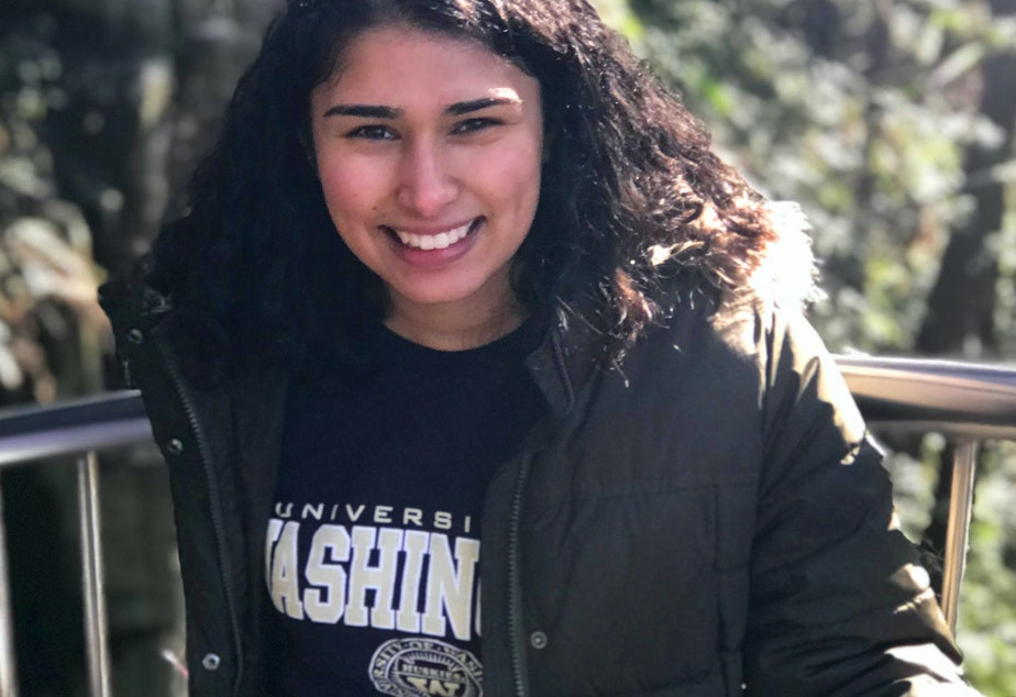 caption: Karishma Vahora poses in a University of Washington sweatshirt in January 2019 when she was a sophomore at UW. Karishma is the first person in her family to go to college.