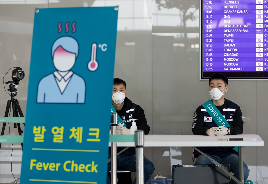 caption: South Korean soldiers wearing protective masks sit at a temperature screening point at Incheon International Airport, South Korea, on March 9.