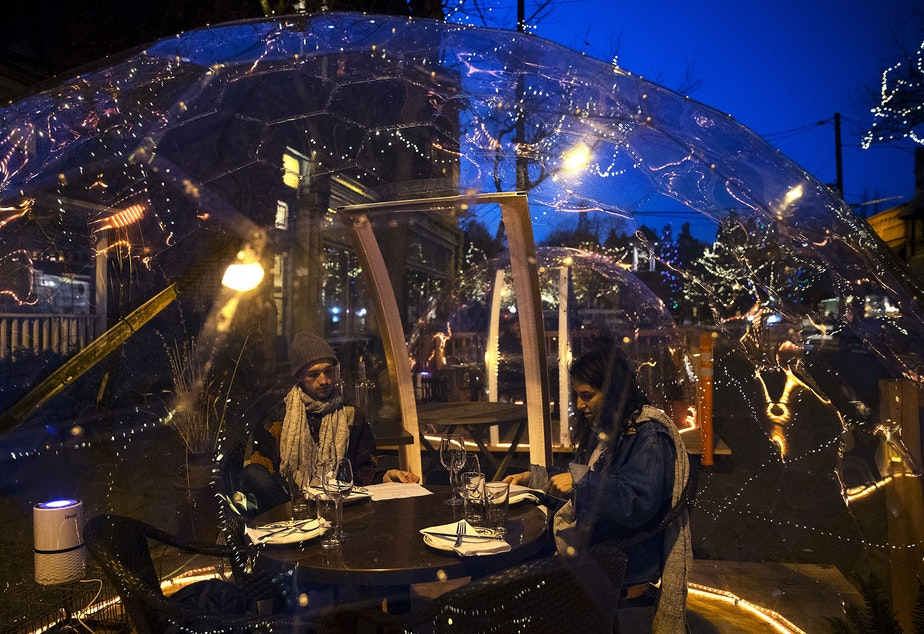 caption: Ben Dines, left, and Alex Manno, right, dine inside of a clear dome structure outside of San Fermo on Sunday, November 15, 2020, along Ballard Avenue Northwest in Seattle.
