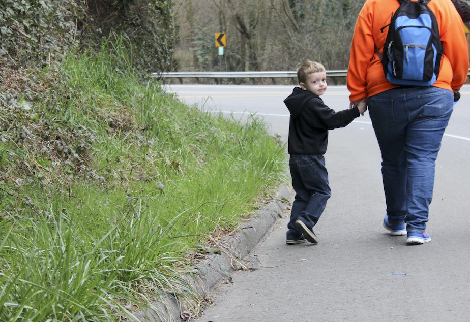 caption: Jessica and Blakely Tossey walk along Kent-Des Moines Road. The busy highway does not have sidewalks so Jessica wears a bright-colored sweatshirt.
