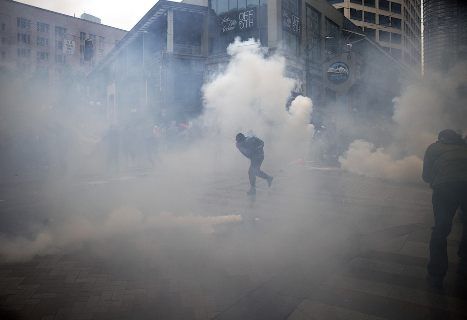 caption: A protester runs from tear gas at the intersection of 5th and Pine Streets on Saturday, May 30, 2020, in Seattle.