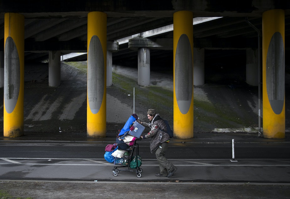 caption: Adrian Anthony moves some of his belongings to another area four blocks away after the encampment where he was living under the I-5 overpass was swept on Wednesday, March 13, 2019, in the Ravenna neighborhood of Seattle. Anthony estimated that a sweep caused him to move from one area to another around 20 times.