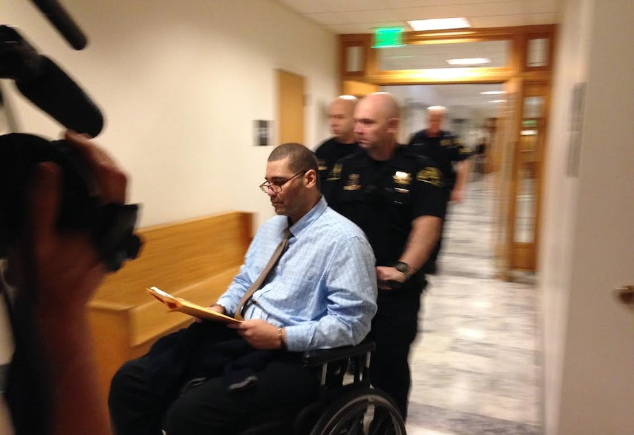 caption: Christopher Monfort is escorted into the courtroom on the first day of his trial for murdering SPD Officer Timothy Brenton, along with other charges, on Tuesday..