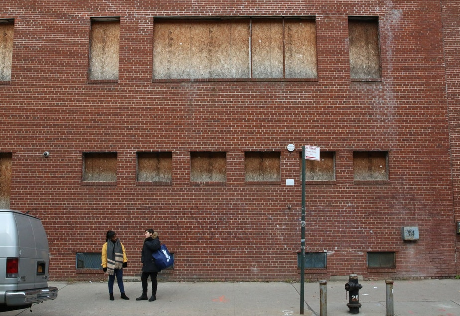 caption: Lena Afridi and Sabrina Jalal stand before a boarded up Queens building on property Amazon will occupy.