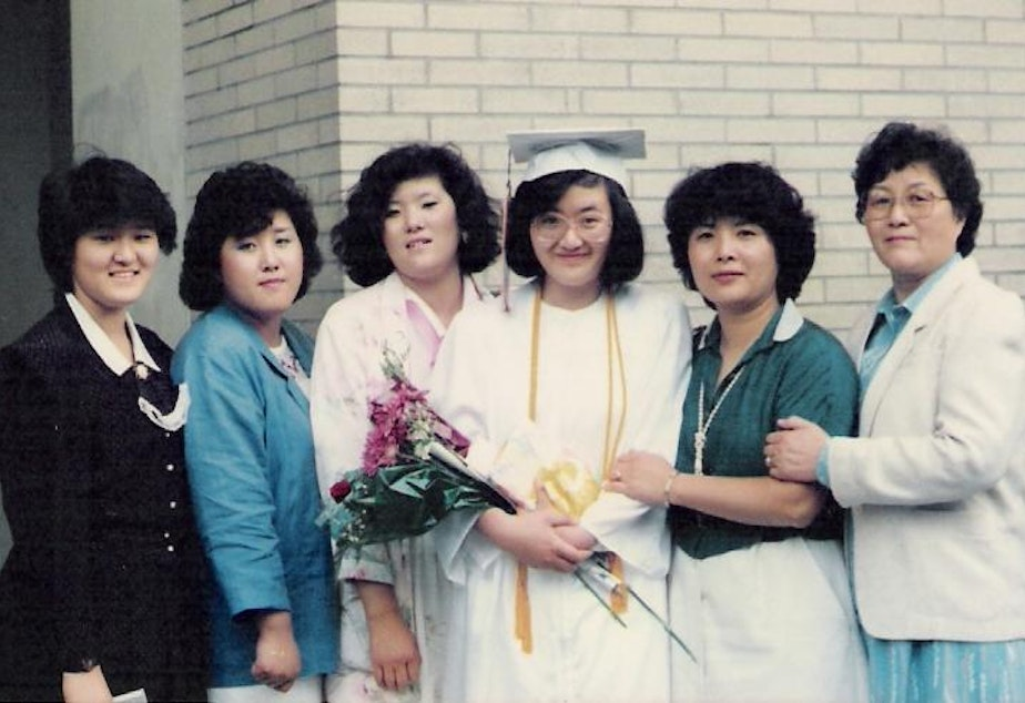 caption: Sue Lim with her mom and four of her sisters (from left: Andria Sueyoung Kim, Jackie Hyekoung Ro, Hyeyoung Lim, Sue Lim, Nancy Junghee Lee, and Eui Bun Lim) at her graduation from Rainier Beach High School in 1986. Sue immigrated to the U.S. at age 16.