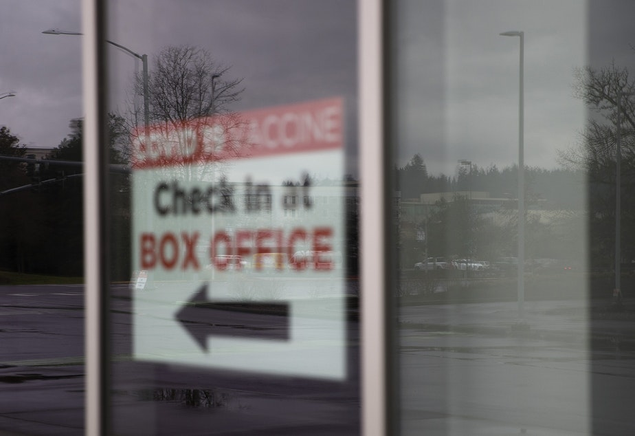 caption: A sign let's people know to check in at the Box Office for a Covid-19 vaccine, on Monday, February 1, 2021, at a new vaccination site at the ShoWare Center in Kent. Six days a week, 500 doses per day will be administered at the site.