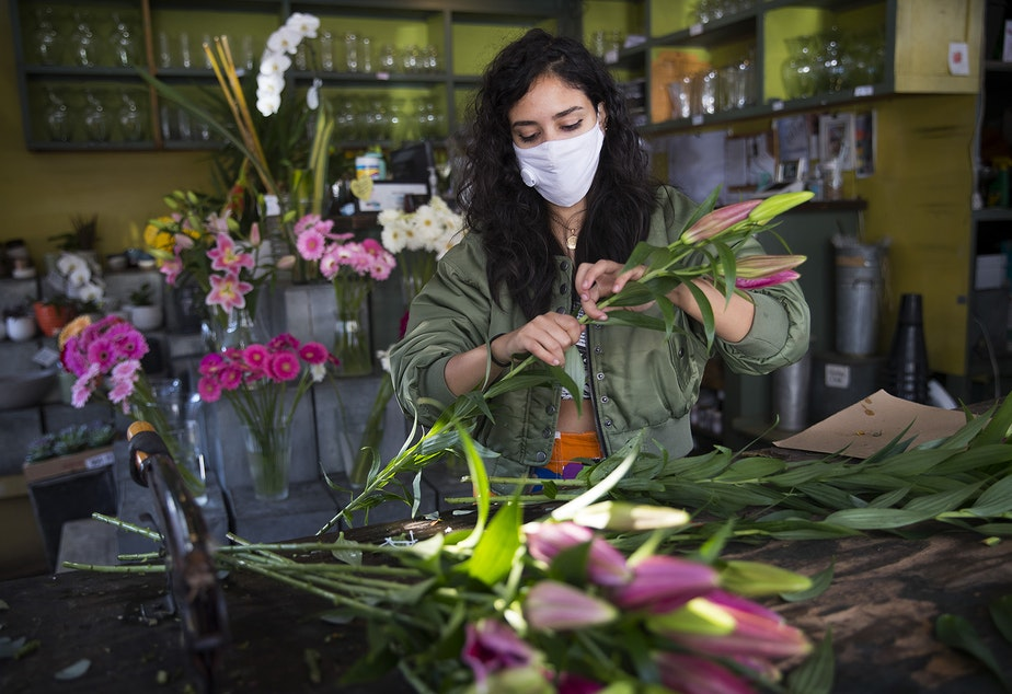 caption: Dory, an employee at Pike Place Flowers, removes leaves while making a bouquet on Friday, October 2, 2020, in Seattle.