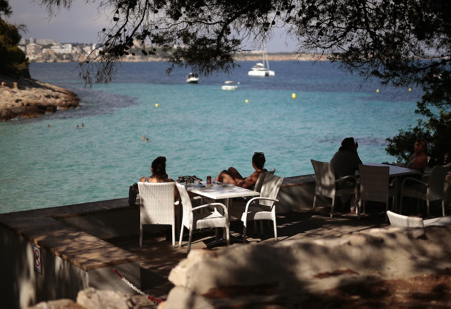 caption: The European Union has decided on its first list of approved travel partners, as part of its reopening of external borders. Here, people sit in a terrace bar at the beach in Palma de Mallorca, Spain, earlier this month, when many internal travel restrictions were lifted.