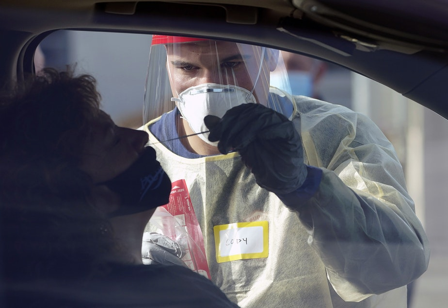 caption: Cody Tupen, a firefighter with the Puget Sound Regional Fire Authority, performs a deep nasal nose-swab COVID-19 test on Nancy Backus, left, the mayor of Auburn, Wash., at a King County COVID-19 testing site in Auburn, south of Seattle, Wednesday, Oct. 28, 2020.