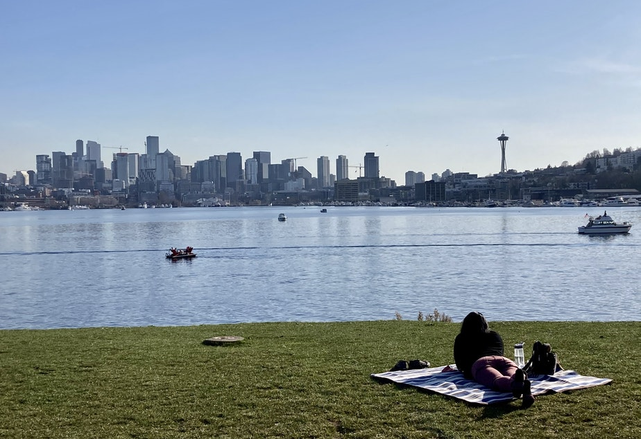 caption: A Gas Works Park visitor faces a clear view of the Seattle skyline on March 3, 2021. Like the park, the waterway was packed with locals enjoying the warmer weather.