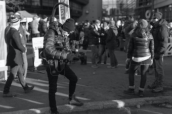 A videographer gathers footage in a crowd.