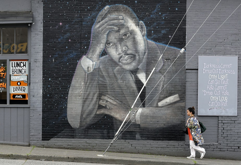 caption: A woman walks past a large mural of the Rev. Martin Luther King Jr. on the side of a diner, painted by artist James Crespinel in the 1990's and later restored, along Martin Luther King Jr. Way, Tuesday, April 3, 2018, in Seattle.