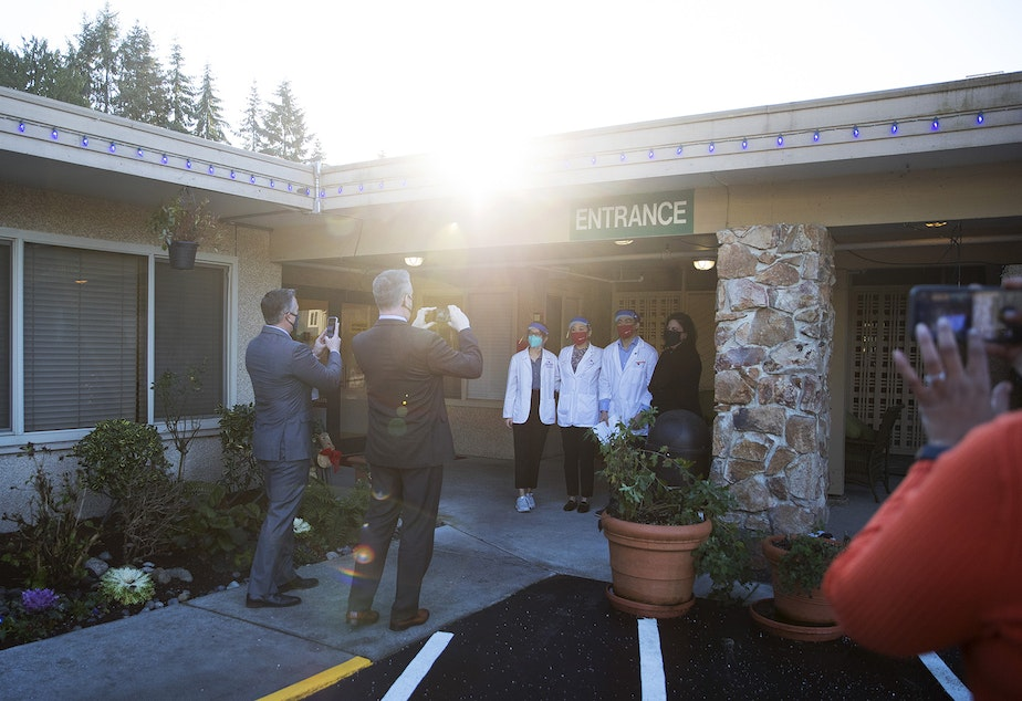 caption: Pharmacists stand near the entrance to the Life Care Center of Kirkland as photographs are taken ahead of the administration of the first Pfizer-BioNTech Covid-19 vaccines on Monday, December 28, 2020, in Kirkland.