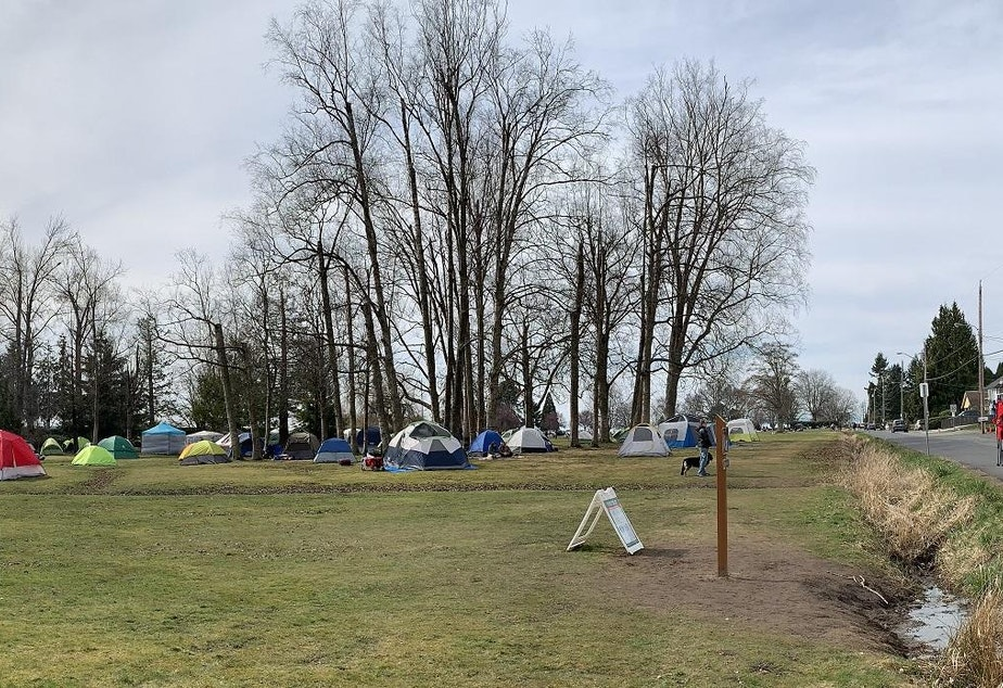 caption: Binational couples set up tents in Peace Arch State Park to give their daytime reunions a little more privacy. The U.S.-Canada border runs along the ditch at right.
