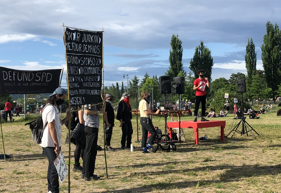caption: Demonstrators gather for a rally in Magnuson Park ahead of a march to confront Seattle Mayor Jenny Durkan at her residence on June 28, 2020.