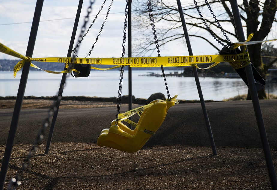 caption: A swing set is surrounded by caution tape at a closed play area as a result of the coronavirus outbreak two days after Gov. Jay Inslee announced the Stay Home, Stay Healthy order, on Wednesday, March 25, 2020, at Seward Park in Seattle.