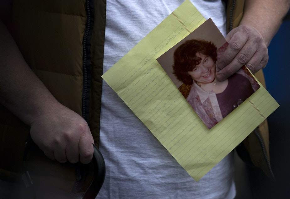 caption: Mike Weatherill holds a picture of his deceased mother, Louise Weatherill, during a press conference held by family members of residents at Life Care Center of Kirkland, outside of the facility on Thursday, March 5, 2020, in Kirkland.