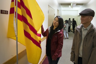 Thanh Tan stands with her father, Duc Tan, as they look at the South Vietnamese flag, at Hung Vuong Vietnamese Language School inside the Lutheran Church of the Good Shepherd on Friday, September 29, 2017, in Olympia.