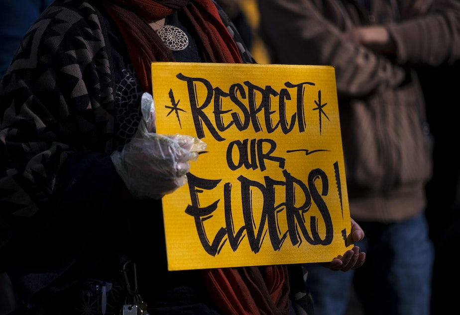 caption: A sign reading 'Respect Our Elders' is shown as hundreds gathered for the 'We Are Not Silent' rally against anti-Asian hate and violence on Saturday, March 13, 2021, at Hing Hay Park in Seattle. Several days of actions are planned by rally organizers in the Seattle area following recent attacks and violence against Asian American and Pacific Islander communities.