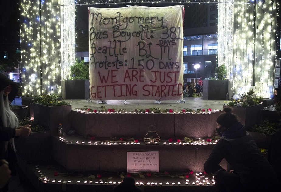 caption: Following speeches from organizers, lit candles were placed around a banner during the 150th day of protests for racial justice in Seattle on Monday, October 26, 2020, at Westlake Park. The other side of the banner reads, 'You can't stop this revolution.'