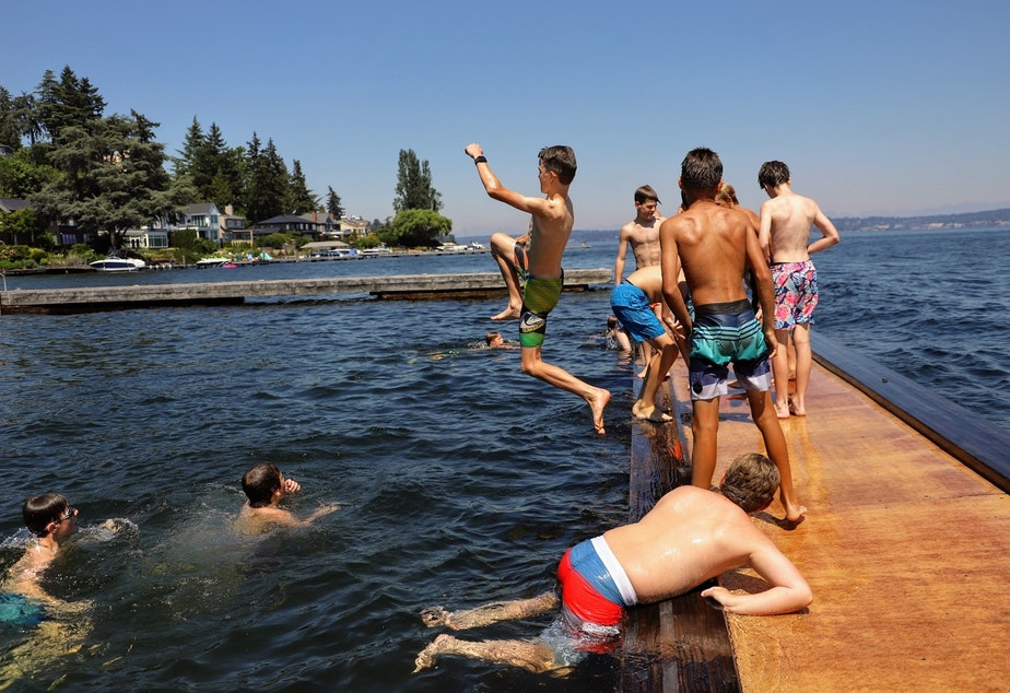 caption: Children jump off the dock at the Laurelhurst Beach Club, a private residential club in Northeast Seattle on Monday, June 28, 2021. Temperatures inched into triple digits, reaching 107 at Sea-Tac Airport.