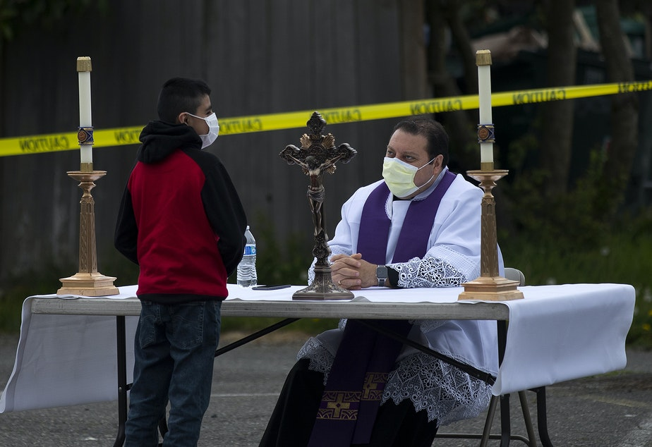 caption: Father Jose Alvarez, right, during walk and drive through confessions on Friday, April 24, 2020, in the parking lot at Holy Family Roman Catholic Church in White Center.
