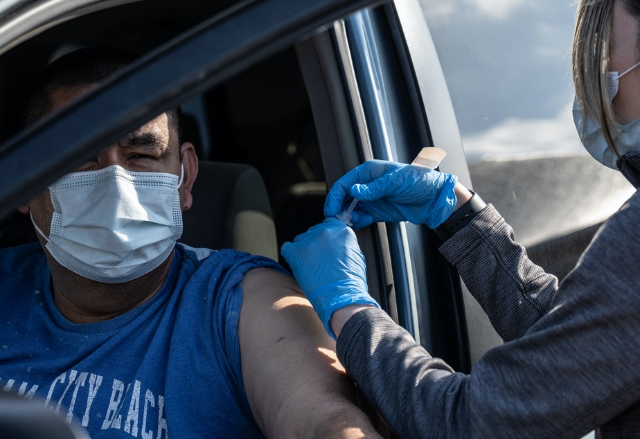 caption: A medical professional from UofL Health administers a vaccine to a patient in their vehicle at University of Louisville Cardinal Stadium.