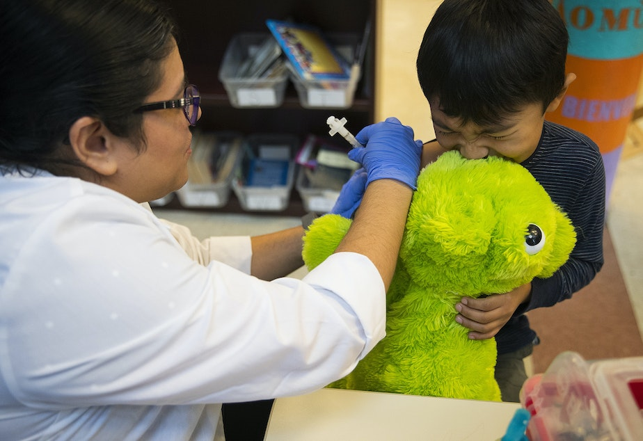 caption: Erika Sandoval, a nurse with the Seattle Visiting Nurse Association, gives kindergartener Javier Garcia Campos a flu shot on Tuesday, October 22, 2019, at Concord International Elementary School in Seattle.