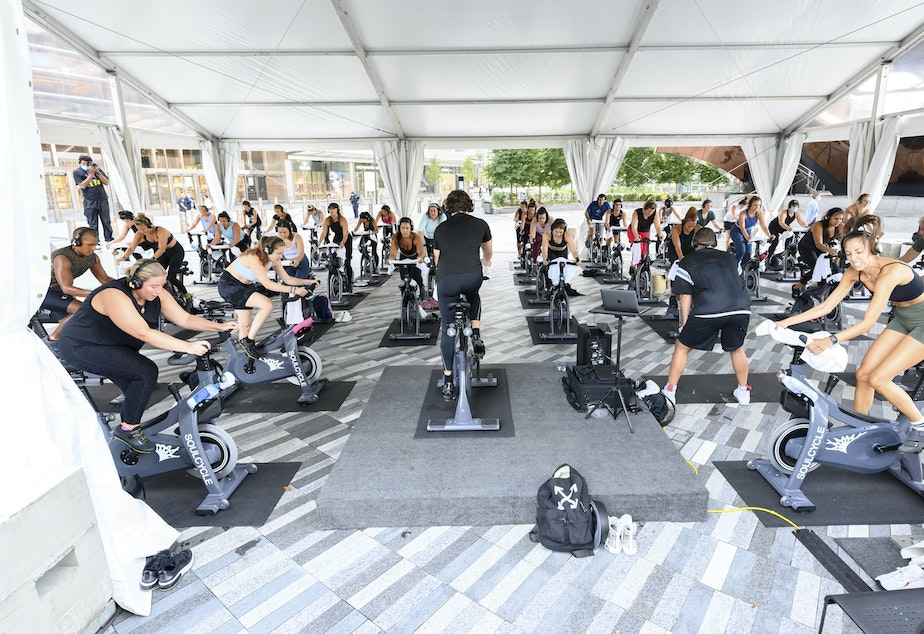 caption: People attend a SoulCycle class under an outdoor tent in September in New York City.