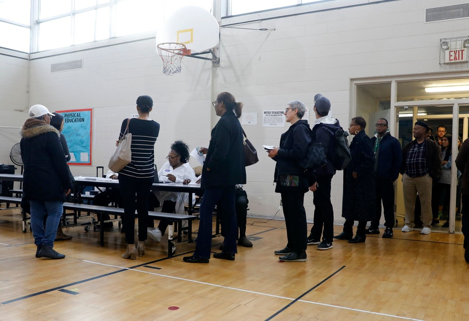 caption: People stand in line at a Detroit polling place during Michigan's March 10 presidential primary. As a result of the pandemic, the state's top election official is sending absentee ballot applications to every registered voter for August and November elections.