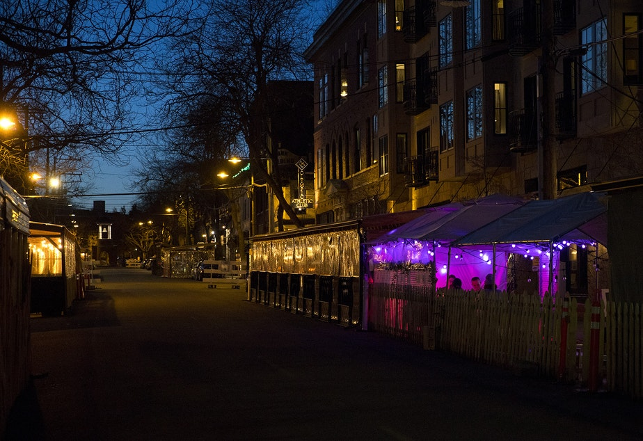 caption: People dine in outdoor dining areas set up along Ballard Avenue Northwest on Monday, March 22, 2021, in Seattle. Beginning Monday, restaurants, retailers, and fitness centers can open with up to 50% capacity as Washington's 39 counties move into the third phase of Gov. Jay Inslee's reopening plan.