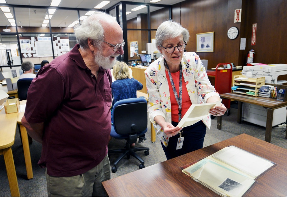 caption: Sue Karren, director of the National Archives in Seattle, shows KUOW listener Ethan Merritt historical photos of the downtown viaduct. June 13, 2019.