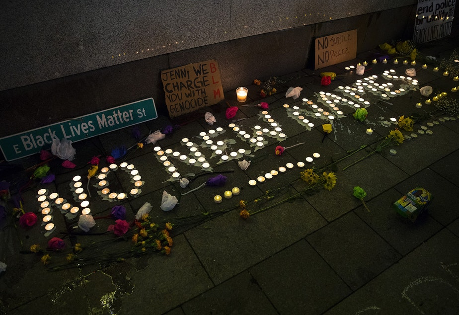 caption: Lit candles spell 'No New Names' during a vigil in honor of a person who was shot and killed by two Seattle Police officers while in a crisis and holding a knife on Tuesday along Seattle's waterfront, on Wednesday, February 17, 2021, at Westlake Park in Seattle.
