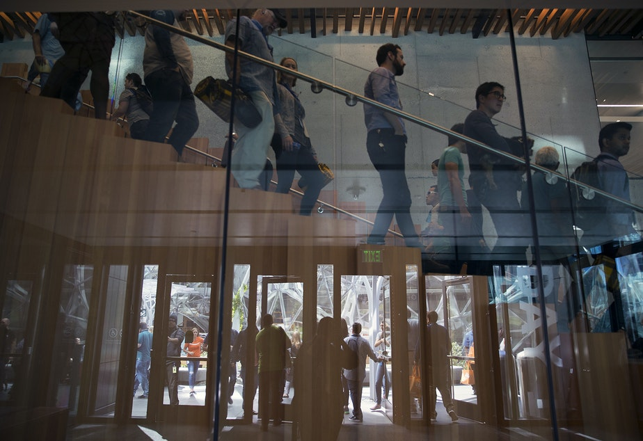 caption: Amazon employees and their parents are reflected leaving the Day 1 Building during Amazon's bring your parents to work day on Friday, September 15, 2017, in Seattle.