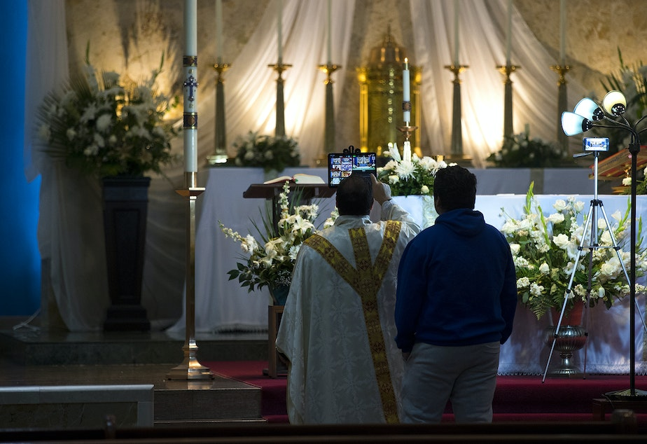 caption: Father Jose Alvarez has help setting up an iPad ahead of a live-streamed daily mass on Friday, April 24, 2020, at Holy Family Roman Catholic Church in White Center.