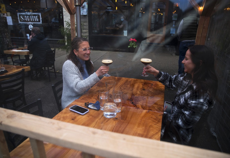caption: Shelby Klemmt, left, and Lexi Newell cheers while dining at Gracia on Monday, March 22, 2021, on Ballard Avenue Northwest in Seattle. Beginning Monday, restaurants, retailers, and fitness centers can open with up to 50% capacity as Washington's 39 counties move into the third phase of Gov. Jay Inslee's reopening plan.