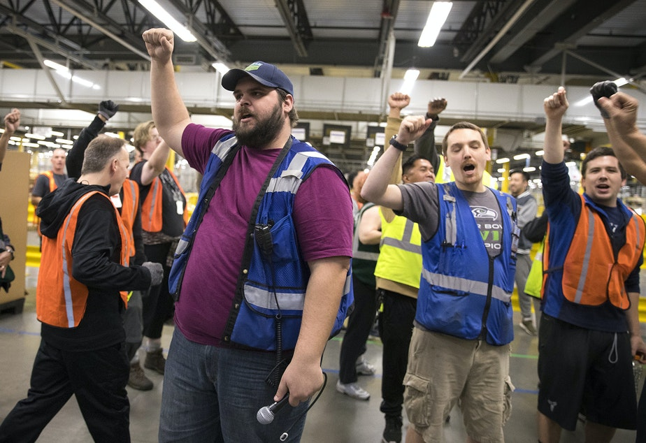 caption: Amazon employee and ship dock manager Zach Mudd, center, leads a group chant as employees return from their lunch breaks at an Amazon fulfillment center on Friday, November 3, 2017, in Kent.