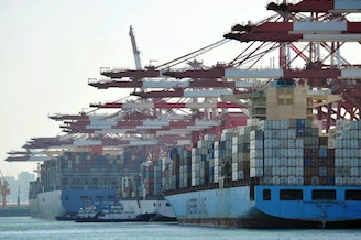 Cargo containers are loaded on ships at a port in Qingdao in China's eastern Shandong province in April. China said it will impose tariffs of 5 percent to 10 percent on $60 billion worth of U.S. products, starting on Monday.