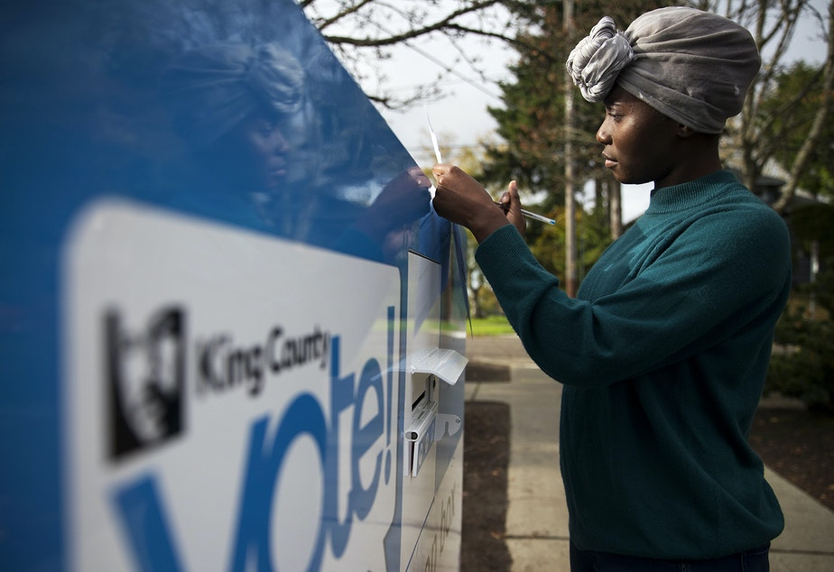 caption: FILE: Fendalene Hegg, 28, signs her ballot on Tuesday, November 6, 2018, at the ballot drop box outside of the Seattle Public Library Beacon Hill Branch in Seattle.