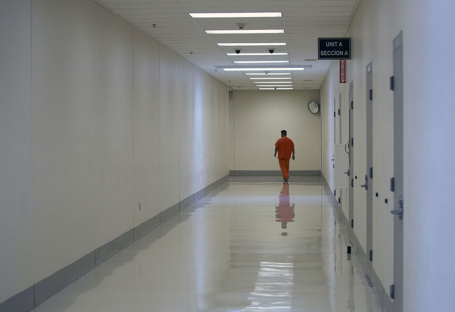 caption: A detainee walks in a hallway on Tuesday, September 10, 2019, at the Northwest Detention Center, recently renamed the Northwest ICE Processing Center, in Tacoma.