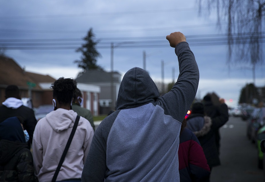 """caption: A man raises his fist in the air while silently marching with about 200 others in honor of 33-year-old Manuel Ellis who was killed by Tacoma police officers after saying """"I can't breathe, sir,"""" one year ago, on Sunday, February 28, 2021, along Martin Luther King Jr. Way in Tacoma."""