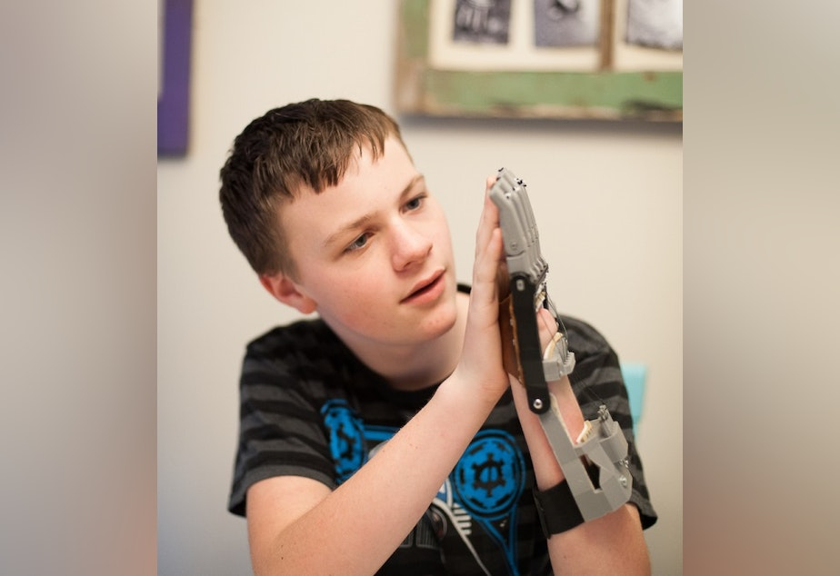 A boy learns to use a hand printed for him by Ivan Owen.