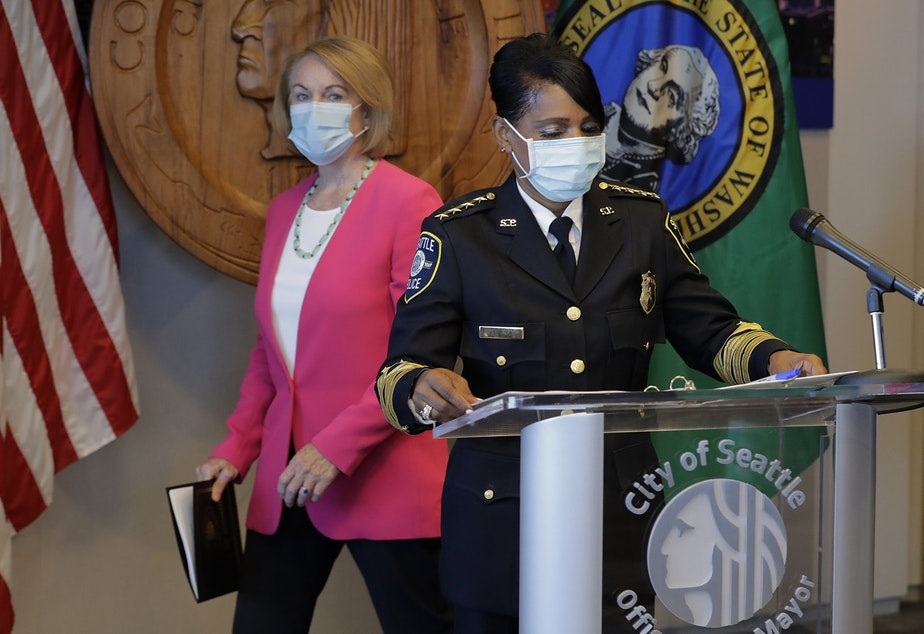 caption: Seattle Police Chief Carmen Best, right, prepares to speak at a news conference as Seattle Mayor Jenny Durkan, left, walks to a socially distanced position, Tuesday, Aug. 11, 2020, in Seattle. Best, the first Black woman to lead Seattle's police department, announced she will be stepping down in September following cuts to her budget that would reduce the department by as many as 100 officers.