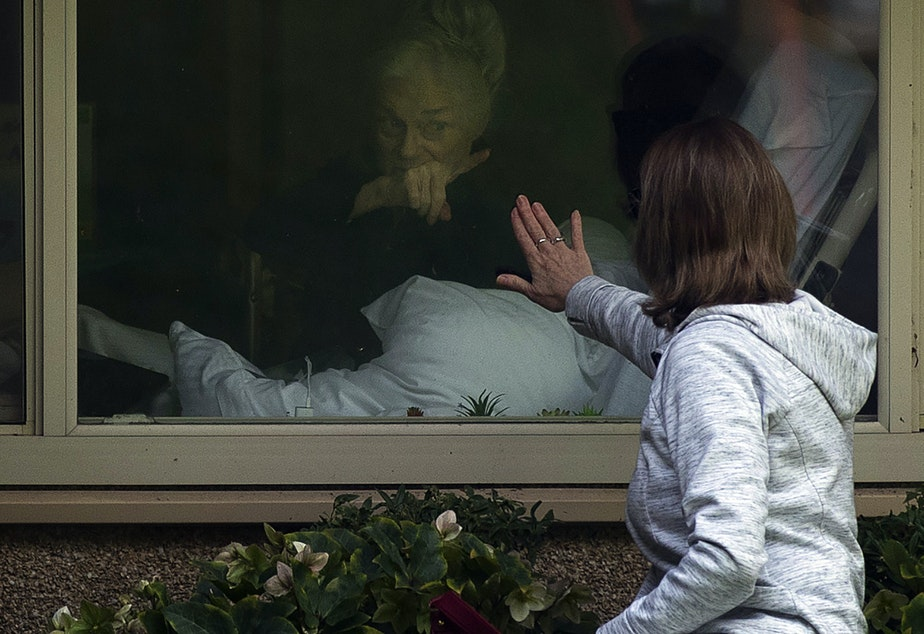caption: Lori Spencer touches the glass of her mother Judie Shape's window while saying goodbye at the Life Care Center of Kirkland, the long-term care facility at the epicenter of the coronavirus outbreak in Washington state, on Wednesday, March 11, 2020, in Kirkland.