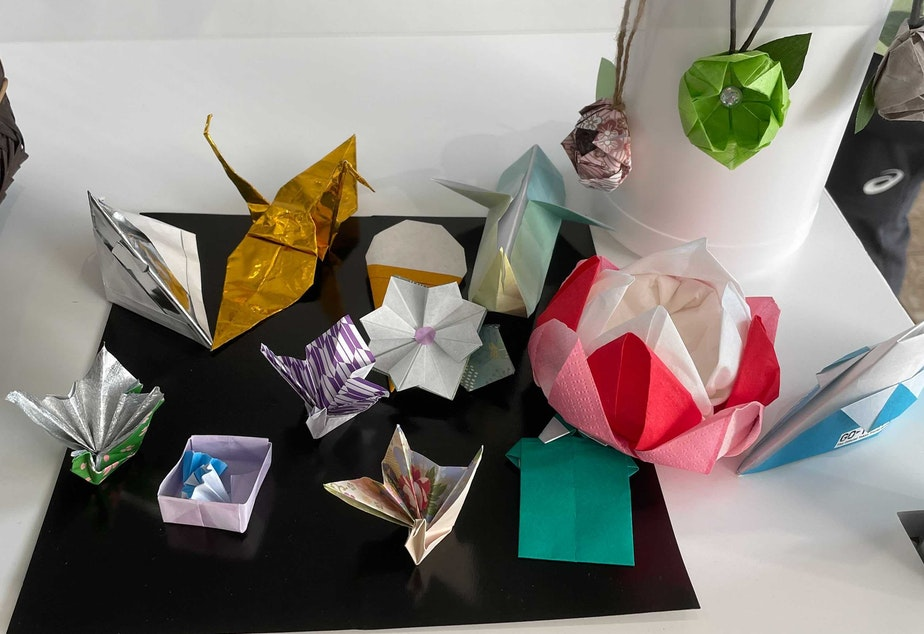 caption: Volunteers at the center for media at the Tokyo Olympics made origami designs, including cranes and flowers.
