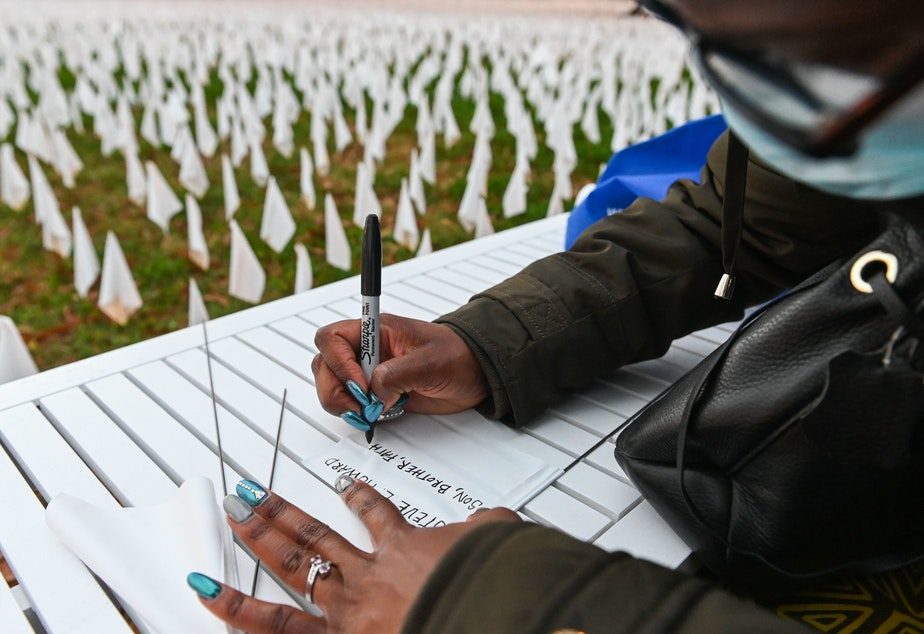 "caption: Patrice Howard writes on white flags before planting them to remember her recently deceased father and close friends in November at ""IN AMERICA How Could This Happen...,"" a public art installation in Washington, D.C. Led by artist Suzanne Firstenberg, volunteers planted white flags in a field to symbolize each life lost to COVID-19 in the U.S."