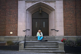 Milee Ballweg sleeps on the steps of a church in Seattle's University District. She's 20, her hair is blonde tinged with pink, and she wears ripped jeans and a Pokémon T-shirt. She sleeps wrapped in gray packing blankets that cover her face.