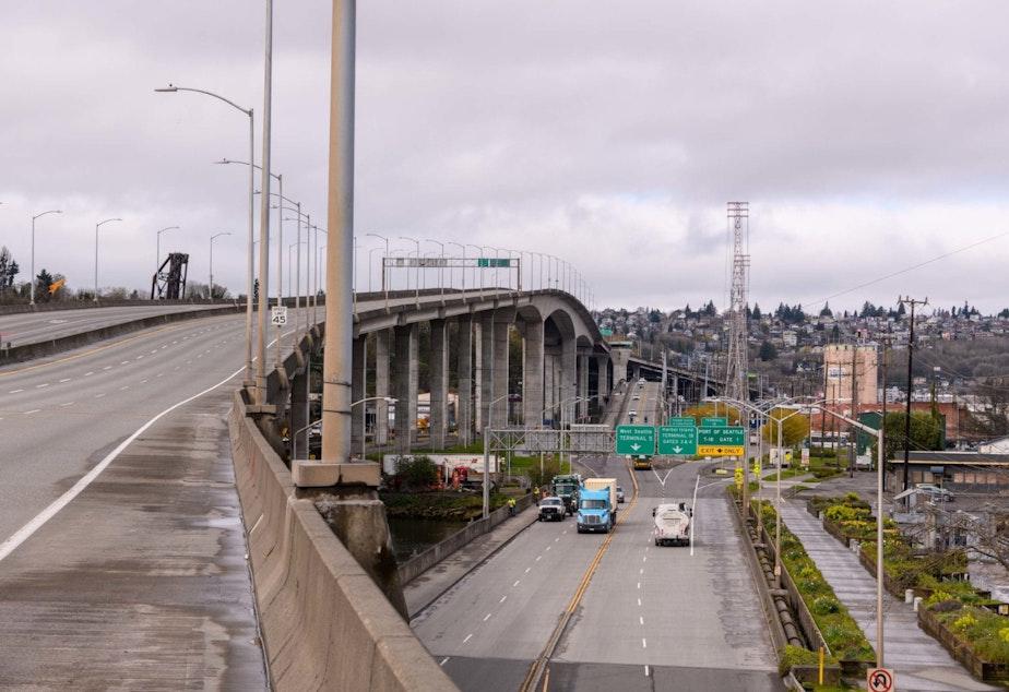 caption: The West Seattle Bridge, closed since March, rises above the Spokane Street Bridge across the Duwamish River.